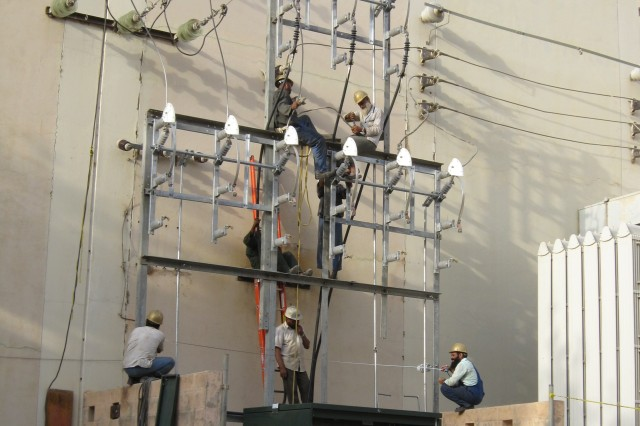 DABS technicians connect the riser cables on the air switch assembly at Kajaki Dam power house in Afghanistan.