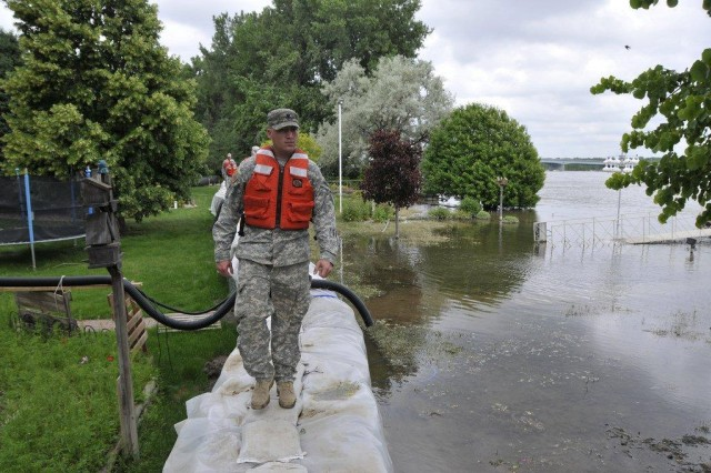 Spc. Sterling Klein, with Detachment 2, 191st Military Police Company, patrols a dike on the south side of Mandan, N.D., July 16, 2011, on a day where the temperature hovered in the mid-90s. The North Dakota National Guard is patrolling dikes around the clock in the Bismarck/Mandan area.