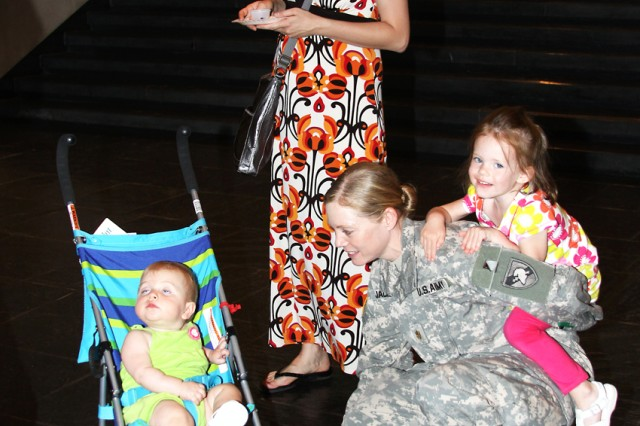Sarah Clark (standing) and daughter Piper (in stroller) talk to Maj. Heather Jackson, Math Department assistant professor, and daughter Bryn at the annual Community Fair July 12. Jackson said this is her family's second time at West Point.