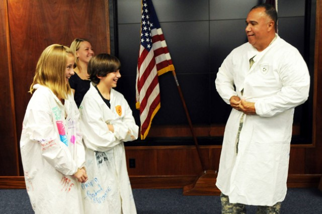 Maj. Gen. Anthony G. Crutchfield, USAACE and Fort Rucker commanding general, tries on the lab coat given to him Friday by graduates of the USAARL's Gains in the Education of Mathematics and Science program as graduates Jacqueline Weiss and James Macklin III, and teacher Sarah Thiel, look on.