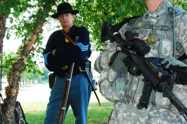 LATHAM, NY- Civil War re-enactor Howard Young, from Rotterdam, NY listens while Sgt. 1st Class Joseph Weidlich, a member of the New York Army National Guard's 206th Military Police Company discusses his  combat gear during a media event conducted at Division of Military and Naval Affairs Headquarters on July 20 to mark the 150th anniversary of the Battle of Bull Run.