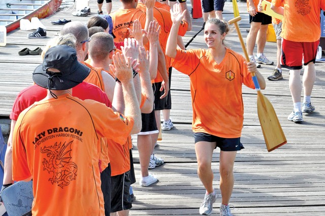 German and American team members high five one another after one of the dragon boat race heats.