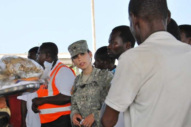 Sgt. Bethany Seymour, a civil affairs sergeant with the Army Reserve's 411th Civil Affairs Battalion, listens as a Ghanaian asks a question about malaria during an outreach visit July 15, 2011, at the harbor of Tema, Ghana.