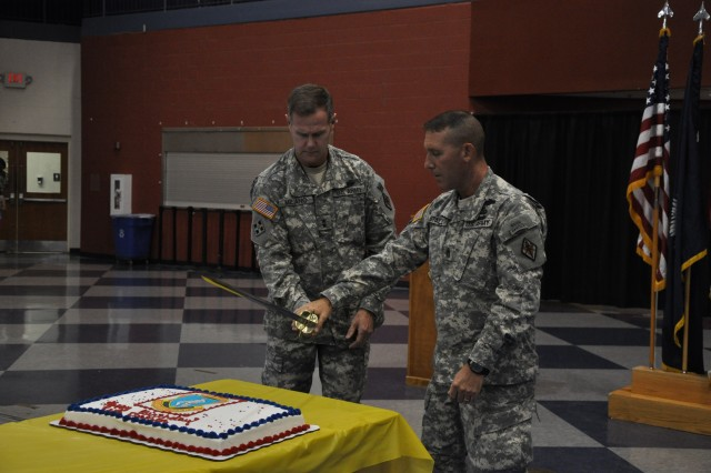 Maj. Gen. James Milano, Fort Jackson's commanding general, and Post Command Sgt. Maj. Brian Stall use a saber to cut the cake at Fort Jackson's 94th birthday celebration at the Solomon Center Friday.