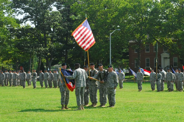 Col. Chipper Lewis, 174th Infantry Brigade commander, and Command Sgt. Maj. Joe Zanders uncase the brigade's colors during a ceremony July 19 at Sharp Field, Joint Base McGuire-Dix-Lakehurst.