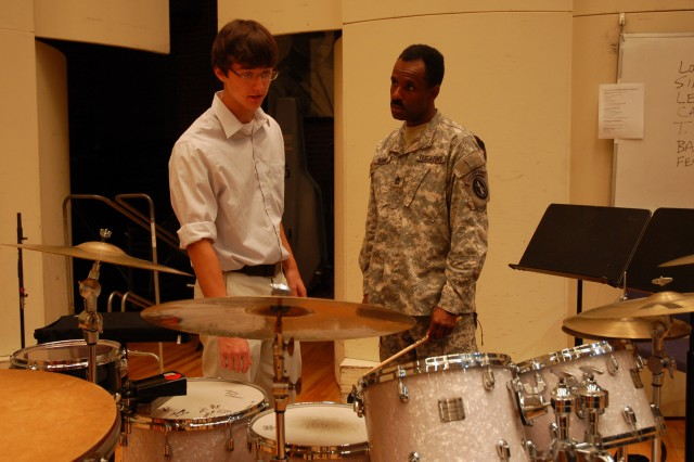 Austin LaPointe, an Arlington Career Center PRIME intern, receives a lesson on various percussion instruments from Sgt. 1st Class Harold Summey, U.S. Army Concert Band. Photo By Rhonda Apple