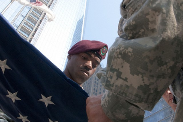 "Staff Sgt. Phillip McNair, a human resource specialist of the 404th Civil Affairs Battalion folds a U.S. flag just after it was raised here at ""Ground Zero"" - the base of the World Trade Center.  This flag has flown over more than 30 different locations in Afghanistan and for the last time here at ""Ground Zero"" on July 20th, 2011.  This flag was flown in every location for exactly 9 minutes and 11 seconds.  This flag was flown originally here during the construction of the World Trade Center before being flown in Afghanistan."