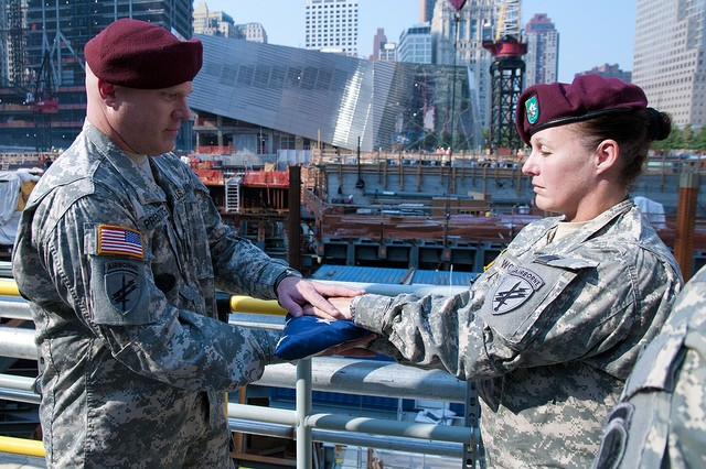 "Lt. Col. Teresa Wolfgang (right), Commander of the 404th Civil Affairs Battalion, hands the U.S. flag to Sgt. 1st Class Rustin Prentice in preparation to raise it for exactly 9 minutes and 11 seconds at ""Ground Zero"" in New York, NY.   The flag was flown originally at ground zero and was raised for the last time here on July 20th, 2011 after visiting more than 30 locations throughout Afghanistan during the 404th's deployment there."