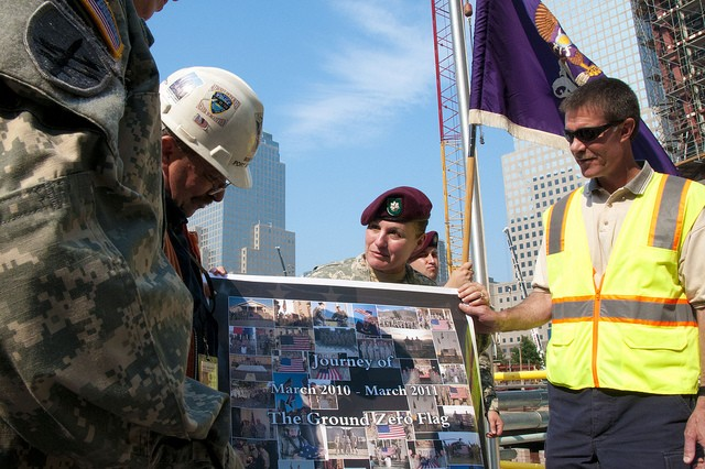 Lt. Col. Teresa Wolfgang (behind poster), Commander of the 404th Civil Affairs Battalion, hands to WTC site manager Bob Schultz, a collection of photos showing where the flag flew in Afghanistan. The flag and photo display will be housed in the WTC museum being constructed.