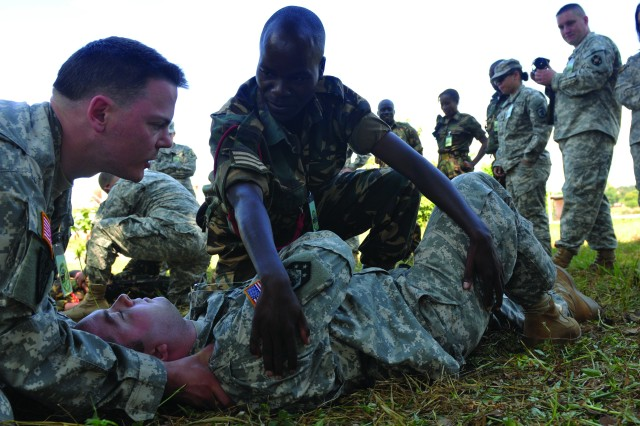 Sgt. Jeffrey S. Niemi of the 399th Combat Support Hospital, assists Sgt. McDonald Linyama of the Malawi Defense Force in assessing Sgt. Robert E. Waight of the 404th Maneuver Enhancement Brigade during training to become a certified combat lifesaver.