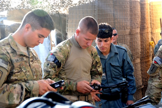 Pfc. Daniel Salcido (left) and Spc. Justin Gleisner (center) synchronize radios as an Afghan Uniformed Police patrolman looks on. The Soldiers and patrolman were part of a team who provided security for the U.S. Army Corps of Engineers in Daykundi province July 13.