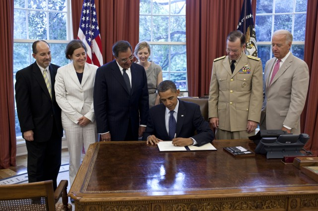 "President Barack Obama signs the certification stating the statutory requirements for repeal of ""Don't Ask, Don't Tell"" have been met, in the Oval Office, July 22, 2011. Pictured, from left, are: Brian Bond, deputy director of the Office of Public Engagement; Kathleen Hartnett, associate counsel to the President; Secretary of Defense Leon Panetta; Kathryn Ruemmler, counsel to the President; Chairman of the Joint Chiefs of Staff Admiral Mike Mullen; and Vice President Joe Biden."