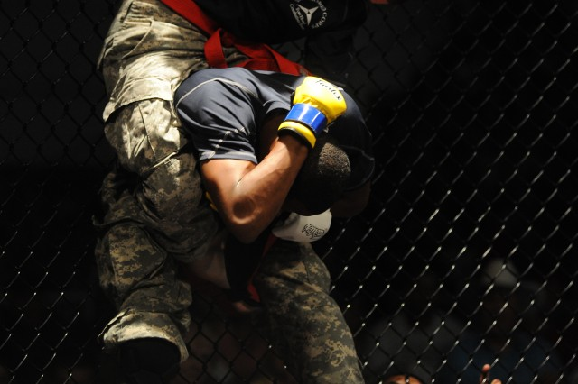 First Lt. David Mason, III Corps, Fort Hood, Texas, delivers a right-handed punch to teammate Spc. Larry Jackson in the bantamweight championship bout in the U.S. Army Combatives Championship at Fort Hood, Texas, July 23, 2011. Mason defended his bantamweight title by defeating Jackson in a unanimous decision.