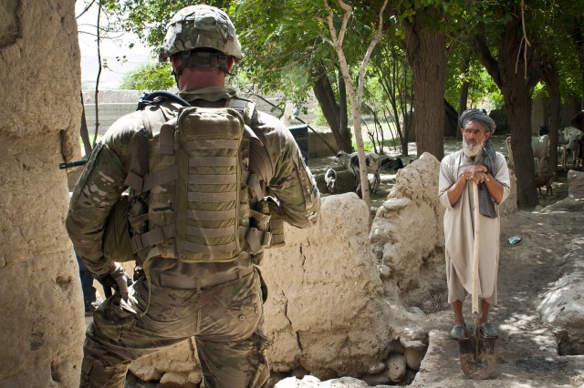 A curious Afghan farmer looks on as Sgt. James A. Jensen, an infantry team leader assigned to Troop C, 3rd Squadron, 4th Cavalry Regiment, Task Force Raider, 3rd Brigade Combat Team, 25th Infantry Division, Task Force Bronco, provides security during a joint-clearing operation in Kot district, Nangarhar province, eastern Afghanistan, July 19, 2011. The operation had about the same number of coalition forces as Afghan National Security Forces.