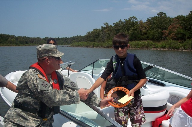"""Lt. Col. Gene Snyman, Tulsa District U.S. Army Corps of Engineers deputy commander, """"tickets"""" a youngster who was caught wearing a life vest at Lake Eufaula July 10, 2011. The ticket is actually a coupon good for a free Frosty frozen treat at any Oklahoma Wendy's restaurant. This is the second year Wendy's has offered this incentive for children to wear a life vest while at the lake. Snyman was out on water patrol with park rangers that day to interact with lake visitors about the importance of water safety."""