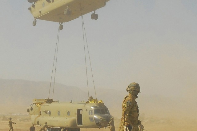 CAMP MARMAL, Afghanistan--A CH-47F Chinook helicopter from Task Force Lobos, 1st Air Cavalry Brigade, 1st Cavalry Division, lowers a sling-loaded Chinook while crew members from 615th Aviation Support Battalion, 1st ACB, help safely guide the aircraft toward the ground, July 6.