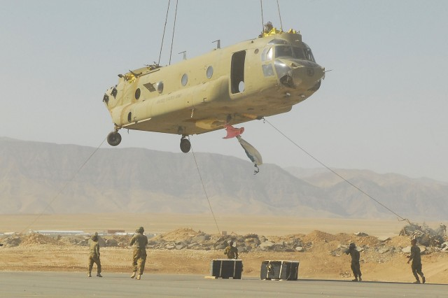 CAMP MARMAL, Afghanistan-- A sling-loaded CH-47F Chinook cargo helicopter from the 1st Air Cavalry Brigade, 1st Cavalry Division, lowers to the ground while crew members from Company B, 615th Aviation Support Battalion, 1st ACB, help guide the aircraft toward the ground, July 6.