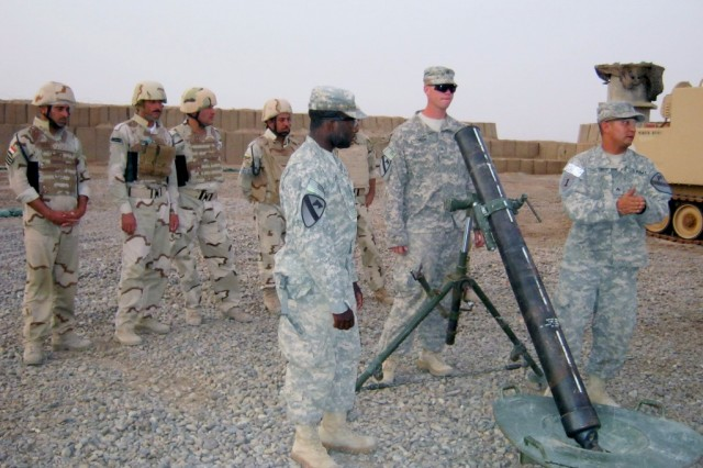 CONTINGENCY OPERATING STATION GARRY OWEN, Iraq - Soldiers from Headquarters and Headquarters Company, 3rd Battalion, 8th Cavalry Regiment, 3rd Advise and Assist Brigade, 1st Cavalry Division, explain how to use a 120mm mortar system, watched by mortar men from the 38th Brigade, 10th Iraqi Army Division on July 4, 2011 at Contingency Operating Station Garry Owen.