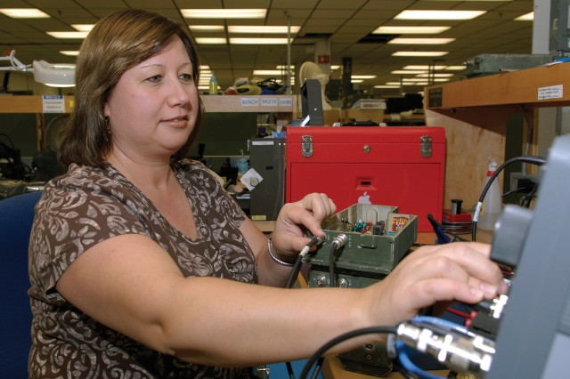 Yelena Raykhel, an electronics mechanic at Tobyhanna Army Depot, performs an electrical test on a Single Channel Ground and Airborne Radio System's frequency amplifier.