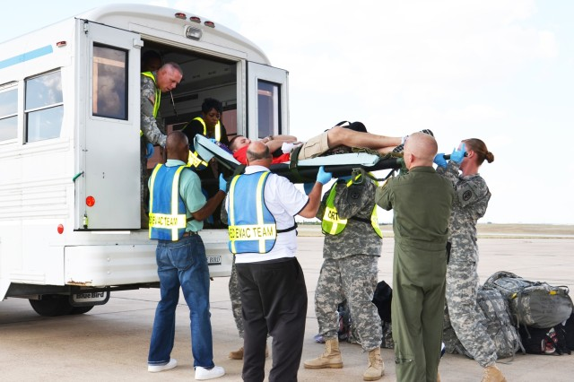 "During a medical evacuation mission July 12, 2011, at Robert Gray Army Airfield at Fort Hood, Texas, the Carl R. Darnall Army Medical Center's Medevac team lifts a patient onto the ambulance for transport back to the hospital. Since beginning its ""Operation Gentle Landing"" Medevac missions in 2003, Darnall now receives almost 200 casualties a month on average, 80 percent of whom are Soldiers with non-combat-related wounds or illnesses."