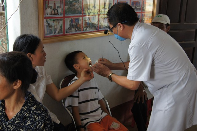 Vietnamese army doctor MD. MS. Nguyen Kien Cuong assists a Vietnamese child during a Bilateral Military Medical Outreach mission in which 18th Medical Command (Deployment Support) and Pacific Regional Medical Command personnel assisted the Vietnamese army July 7-18
