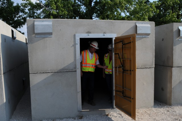 U.S. Army Corps of Engineers quality assurance specialist Lucia Gamba (right) and area engineer Don Braun inspect newly placed storm shelters at the temporary replacement site for Irving Elementary School in Joplin, Mo., July 2, 2011.