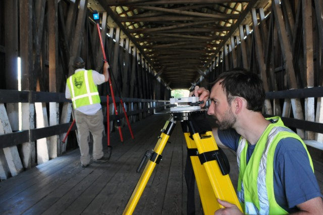 Architect Jeremy Mauro (right) with the Historic American Engineering Record prepares a level while lead architect Christopher Marston adjusts a target in preparation for a laser scan of the Knights Ferry Covered Bridge at the U.S. Army Corps of Engineers Sacramento District's Stanislaus River Parks near Oakdale, Calif., June 15, 2011. (U.S. Army Photo/Hunter Merritt)