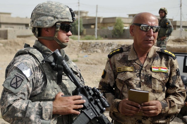 First Sergeant Steven Sierras, Company A, 2nd Battalion, 12th Cavalry Regiment, 1st Advise and Assist Task Force, 1st Infantry Division, discusses plans with a member of the expanded Combined Security Force prior to a patrol north of Kirkuk City, Iraq, July 19, 2011. U.S. forces assumed an advisory-only role as the eCSF began operations as a full-strength battalion following the addition of a third company of members, July 18.