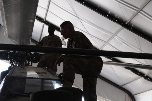 KANDAHAR AIRFIELD, Afghanistan (June 22, 2011) - An AH60D Apache helicopter crew chief with Troop D, Task Force Palehorse (7th Squadron, 17th Cavalry Regiment), examines a blade to determine whether it needs repair or replacement here June 22. Many helicopter maintainers strive to advance to crew chiefs and eventually advance farther.