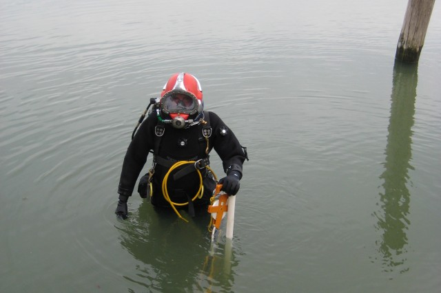 A diver suited in surface supplied air (SSA) dive equipment stands near the downstream end of the submerged Clarksburg Ferry. Maximum water depths at the time of the investigation were 17 feet with the longest dive being 1.5 hours in length.