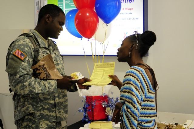 Belinda Ganes-Hager, Army Community Service Outreach Program coordinator, speaks with Pfc. Cameron Daniel, 560th Battle Surveillance Battalion, about ACS and its many benefits at the Post Exchange, July 25.