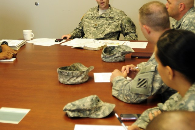 Major George Wallace, 1st Heavy Brigade Combat Team chaplain, speaks with his chaplains and chaplain's assistants during a weekly meeting at the 1st HBCT Headquarters, July 21.