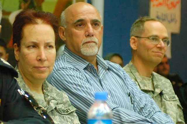 Lieutenant Colonel Deborah Anne Freiberg, 403rd Civil Affairs Battalion, left, and Chaplain (Maj.) Peter Dissmore, brigade chaplain, 1st Advise and Assist Task Force, 1st Infantry Division, right, listen to a speaker during a conference promoting ethnic diversity and cooperation at the Chaldean Cathedral's Visitor Center in Kirkuk, Iraq, July 18, 2011.