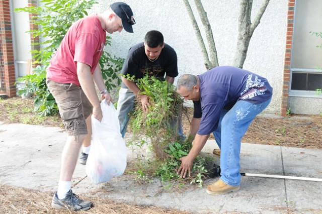 Maj. John Tucker, 1st Bn., 14th Avn. Regt. executive officer, Fernando Rivera Jr., and 1st Bn., 14th Avn. Regt. 1st Sgt. Fernando Rivera, clean up recently cut weeds and brush at D.A. Smith Middle School in Ozark Saturday. The unit's command group volunteered to help with the school's cleanup day in preparation for the beginning of the new school year.