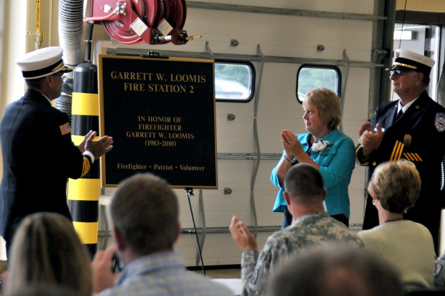 Peter Queior, left, retired Fort Drum fire chief, helped Gary and Amy Loomis, parents of Garrett Loomis, unveil a plaque created in their son's honor during the Garrett W. Loomis Fire Station 2 dedication ceremony July 26. Gary Loomis, seen in uniform, is a retired assistant fire chief from Fort Drum and former Sackets Harbor volunteer firefighter.
