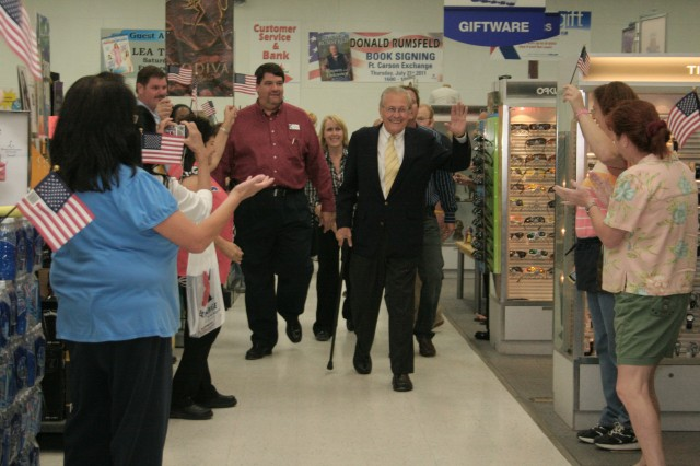 FORT CARSON, Colo. -- Fort Carson Post Exchange employees and customers line the aisle waving American flags to welcome former Secretary of Defense Donald Rumsfeld for his book signing July 21.