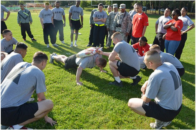 "Staff Sgt. Danial Zweifel does pushups for Company C, 53rd Signal Battalion during the ""Dog Food Push Up"" event of the Vogelweh Commissary's Appreciation Day June 24."