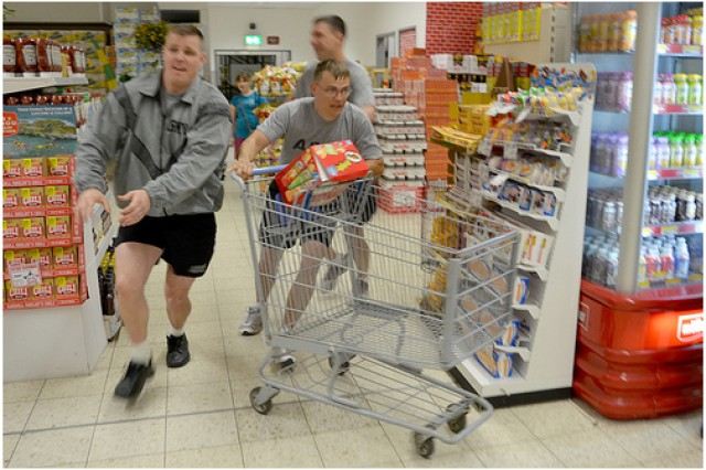 "Staff Sgt. Michael Landry, Sgt. Toby Hensley, and Spc. Theodore Furrow start the ""Commissary Sweep"" for Company C, 53rd Signal Battalion during the Vogelweh Commissary's Appreciation Day June 24."