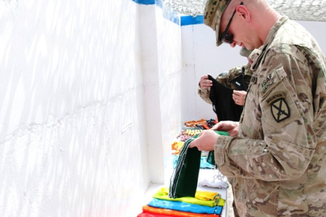A Soldier with 3rd Brigade Combat Team looks through a variety of handmade scarves at the craft fair July 17 at the Zharay District Center.