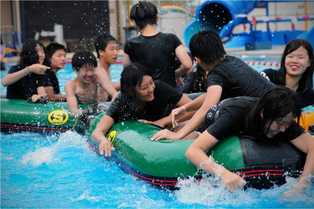 """Students from Waegwan Middle School paddle with their hands during a boat race conducted during an """"English camp"""" held at USAG Carroll July 26, 2011. The 7th annual English camp  ran from July 25-29, 2011.  The five-day camp is part of U.S. Forces Korea's Good Neighbor Program and  is provided for students at Waegwan Middle School.  It is designed to enhance cultural awareness and provide Korean students an opportunity to use, improve, and develop confidence in the English language skills through interaction with native English speakers. Photo by Pfc. Sung Kwang-jae"""