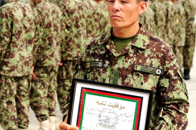 Afghan National Army Private Mohammed Khaili, the 100,000th Basic Warrior Training graduate to go through literacy training, displays a plaque and pen he was awarded  in recognition of the Afghan National Security Force's accomplishments in education at Kabul Military Training Center in Kabul, July 28. (Navy photo by Petty Officer 2nd Class Michael James)