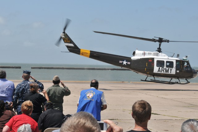 The crowd gathered to honor the last UH-1H Huey offers a final salute as the Viet Nam era helicopter lifts off from the flightline at Corpus Christi Army Depot, June 21, 2011. U.S. Army Photo by Ervey Martinez (RELEASED).