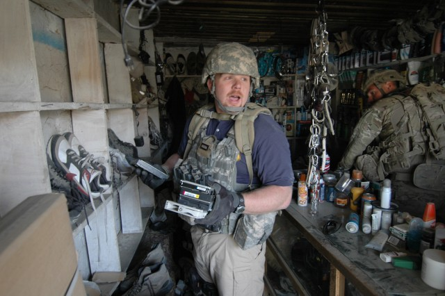 Special agent Chris Wallace, the special sexual assault investigator for Fort Campbell, Ken., currently deployed with the 10th MP Battalion (CID) (ABN), recovers stolen hard drives and sensitive items that were hidden during a raid June 1, 2011, in Bagram, Afghanistan.