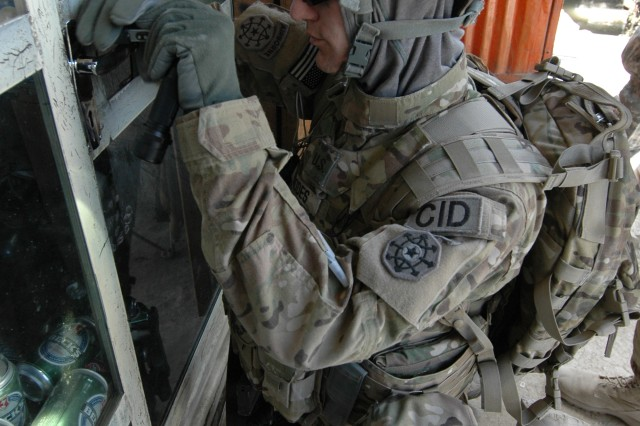 Special agent Russell Rhodes, a Criminal Investigation Division special agent and digital forensic examiner with the 5th Military Police Battalion (CID) currently serving with the 10th Military Police Battalion (CID) (ABN) in Bagram, Afghanistan, picks the lock of a store believed to be selling stolen U.S. Government property.