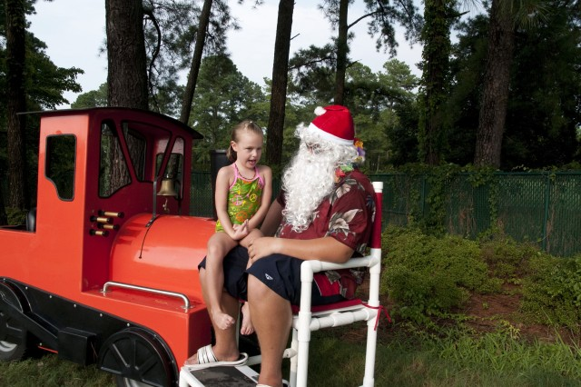 "Emily Irwin, 5, a Fort Bragg Family member, tells Santa what she wants for Christmas at the FMWR Christmas in July event Saturday at Normandy Pool. The event featured a ""dive-in"" move, 'Polar Express,' a visit from Santa and iced chocolate."