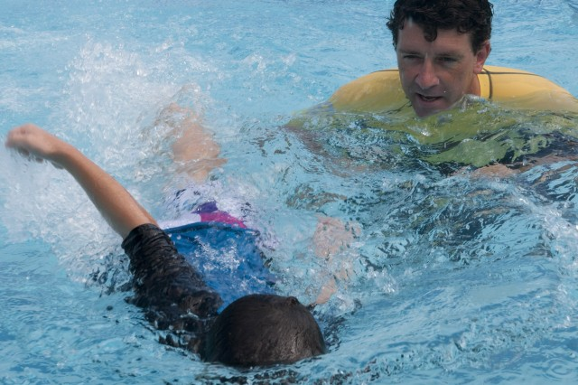 Instructor Oscar Roverato, oversees the swim stroke of Ian Masterson, 7, during the Fighting Fish Swim Camp, Monday, at Normandy Pool. Students learn to improve  techniques such as the backstroke and mastering timing of kicks and arm coordination to ensure proficiency.