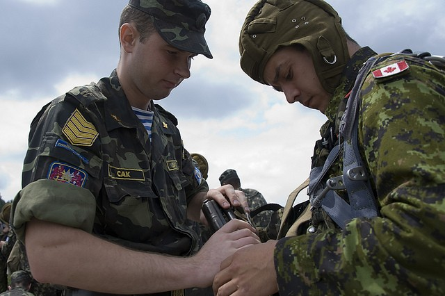A Ukrainian Paratrooper assists Cpl. Jonathan Prévost, Parachute Rigger from 3rd Battalion, Royal 22nd Regiment, with his AKS-74 Assault Rifle prior to a parachute jump during Exercise Rapid Trident 2011.