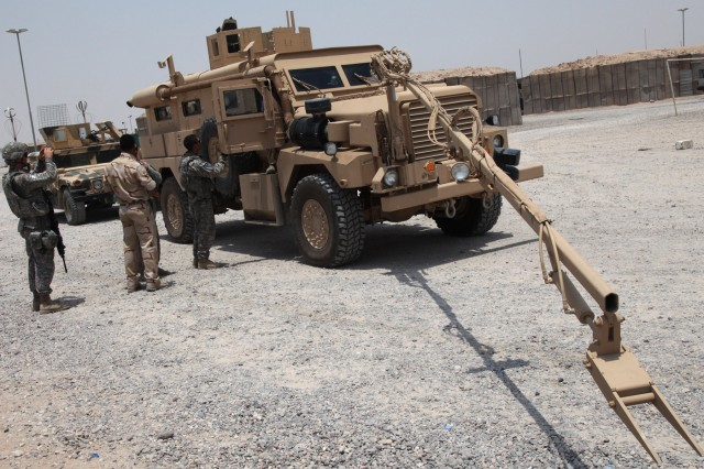 CONTINGENCY OPERATING BASE BASRAH, Iraq – Soldiers from Headquarters and Headquarters Company, 1st Battalion, 12th Cavalry Regiment, 3rd Advise and Assist Brigade, 1st Cavalry Division instruct Iraqi Army engineers on use of the interrogation arm used for route clearance July 12, 2011.