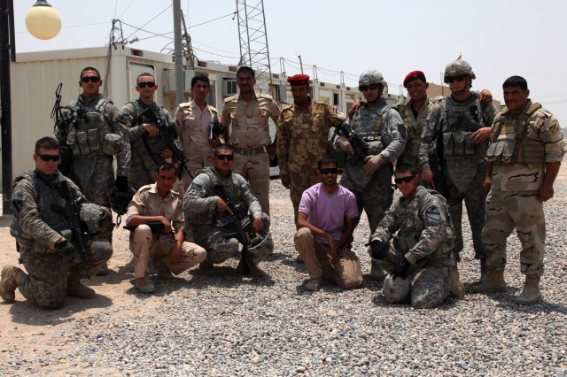 CONTINGENCY OPERATING BASE BASRAH, Iraq – Soldiers from Headquarters and Headquarters Company, 1st Battalion, 12th Cavalry Regiment, 3rd Advise and Assist Brigade, 1st Cavalry Division, pose for a picture with their Iraqi Army counterparts before embarking on a partnered route clearance patrol July 12, 2011.