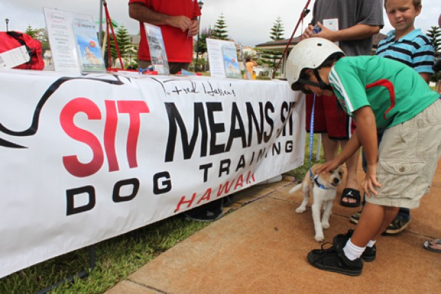 "Sebestian Carabalo, an Army family member, pets Adolf, a 9-week-old Border Collie mix, during the ""Pets Are People Too Expo,"" held at the Porter Community Center, Schofield Barracks, July 21."